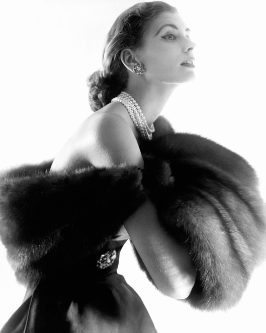 Suzy Parker modeling fur stole, pearl necklace, and jeweled earrings