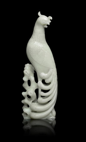 A rare very pale green jade carving of a phoenix on rockwork